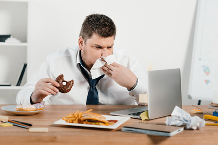 overweight businessman eating donuts, hamburger and french fries while wokring with laptop in office