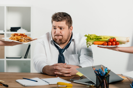 fat businessman choosing healthy or junk food at workplace in office Banco de Imagens