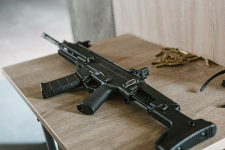 black rifle with bullets on wooden table in shooting range Banco de Imagens - 104559224