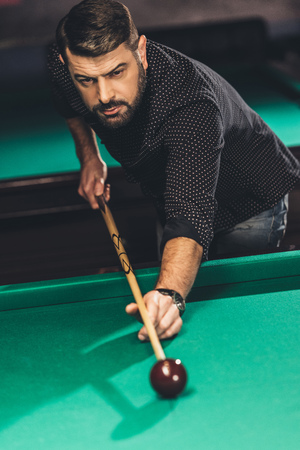 front view of handsome man playing in pool at billiard bar Stock Photo