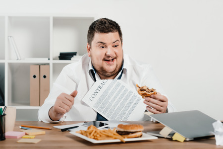 fat businessman eating hamburgers and french fries in office Banco de Imagens