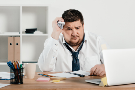 overweight businessman working with notepad and laptop in office