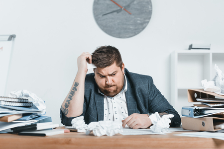 confused overweight businessman in suit working with documents in office