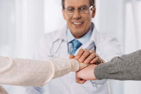 cropped image of doctor and two patients holding hands