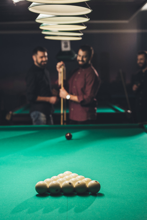 smiling man rubbing cue with chalk beside pool table at bar with friends