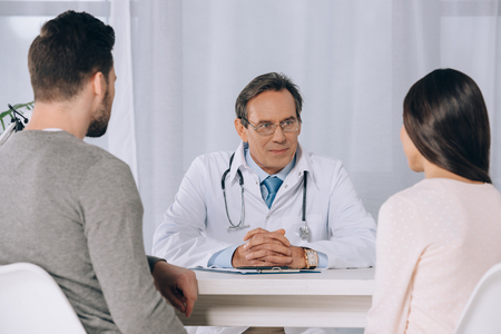 doctor talking to young couple at clinic