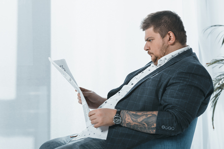 overweight businessman in suit reading business newspaper in office