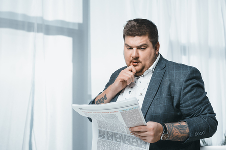 thoughtful overweight businessman in suit reading newspaper in office