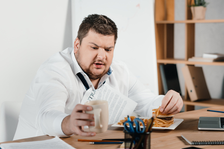 overweight businessman eating fast food and drinking coffee in office Banco de Imagens