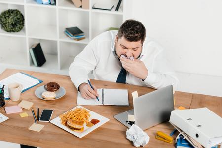 Empresario con sobrepeso comiendo donuts, hamburguesas y papas fritas mientras wokring en Office