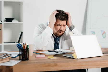 overweight businessman with headache using laptop in office