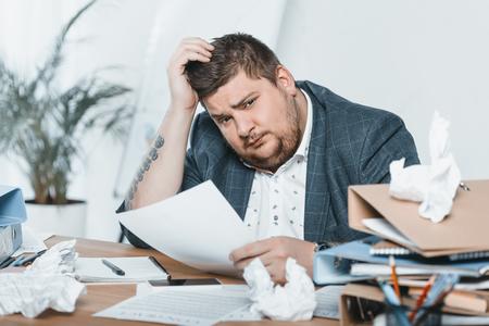 fat businessman in suit doing paperwork in office Banco de Imagens