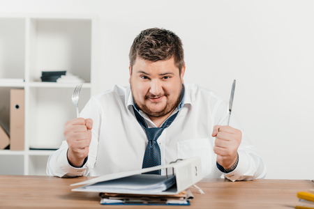 overweight businessman with fork and knife sitting at table with folders Imagens