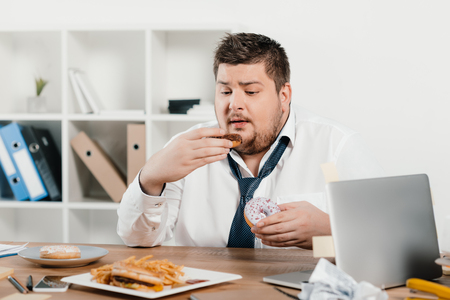 overweight businessman eating donuts, hamburger and french fries at workplace
