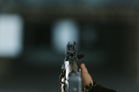 cropped image of man aiming rifle at target in shooting range