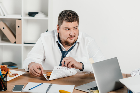 fat businessman sitting at workplace in office
