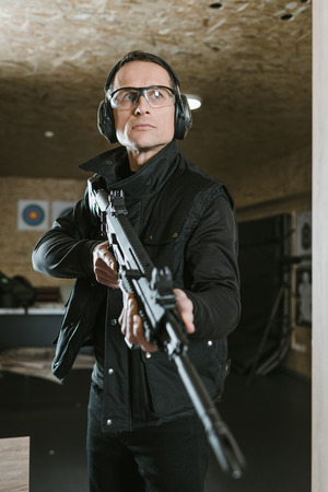 handsome man with rifle in shooting range Stock Photo