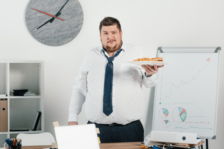 fat businessman with junk food in office