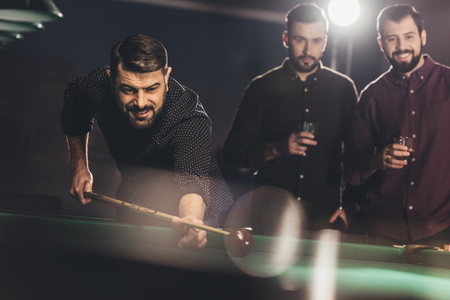 successful man playing in pool at bar with friends Stock Photo