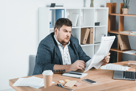 fat businessman in suit reading newspaper at workplace