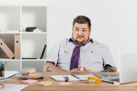 overweight businessman looking at doughnuts while sitting in office
