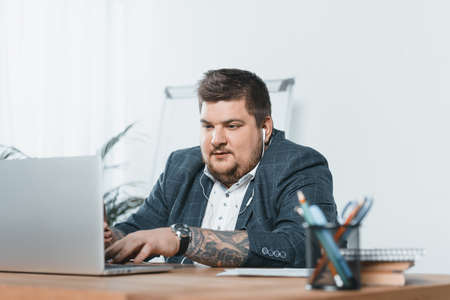 overweight businessman listening music with earphones while working on laptop in office