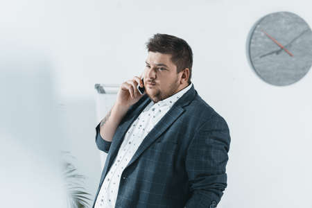 overweight businessman talking on smartphone in office Banco de Imagens