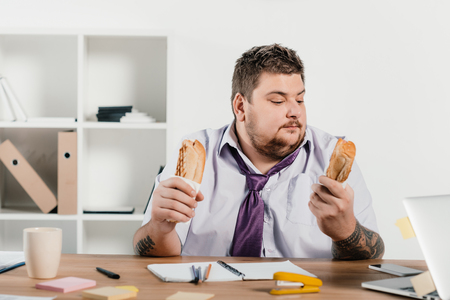 overweight businessman eating hotdogs at workplace in office Banco de Imagens