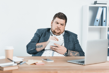 overweight businessman in suit writing in notepad and working with laptop at workplace Banco de Imagens