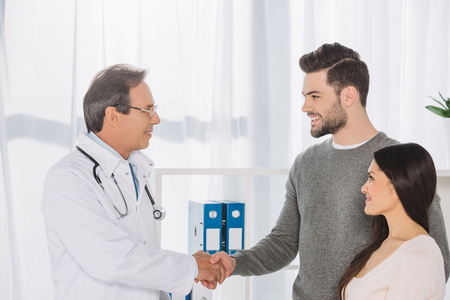 doctor and smiling patient shaking hands Stock Photo