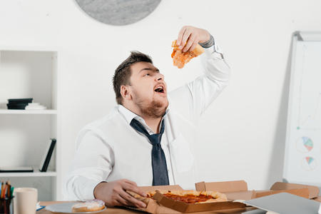 overweight businessman eating pizza for lunch at workplace Banco de Imagens