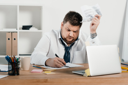 overweight businessman working with documents and laptop in office Banco de Imagens