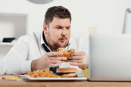 Empresario con sobrepeso trabajando mientras come hamburguesas y papas fritas en la oficina