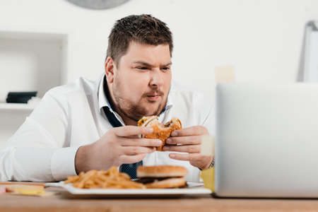 overweight businessman working while eating hamburger and french fries in office 스톡 콘텐츠
