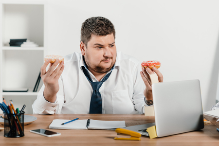 overweight businessman eating donuts at workplace