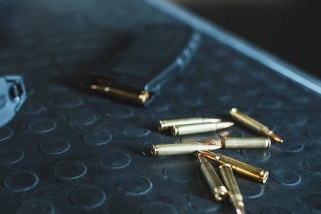 Vista cercana de balas y cargador de rifle en la mesa