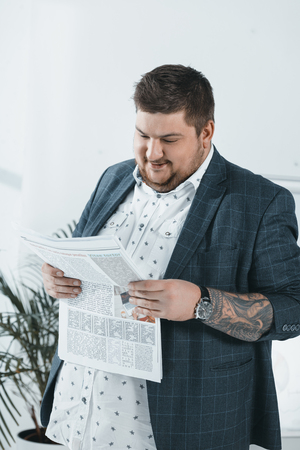 fat businessman in suit reading newspaper in office Banco de Imagens