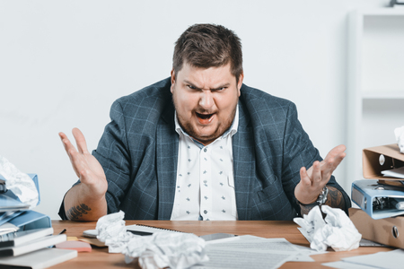 angry overweight businessman in suit working with documents in office Banco de Imagens