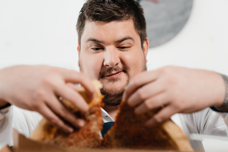 selective focus of overweight businessman eating pizza for lunch at workplace