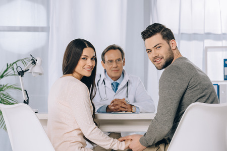 happy couple holding hands at clinic Stock Photo