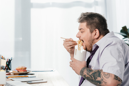 overweight businessman eating noodles at workplace in office Banco de Imagens