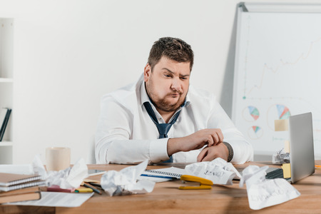confused overweight businessman sitting at workplace with crumpled papers Banco de Imagens