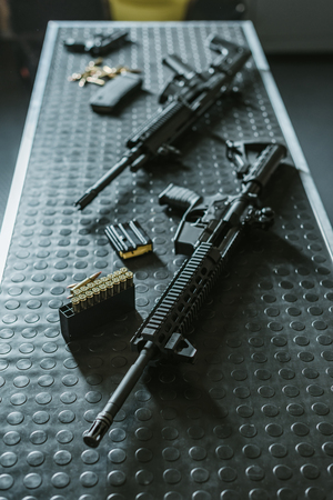 high angle view of rifles with bullets on table in shooting range