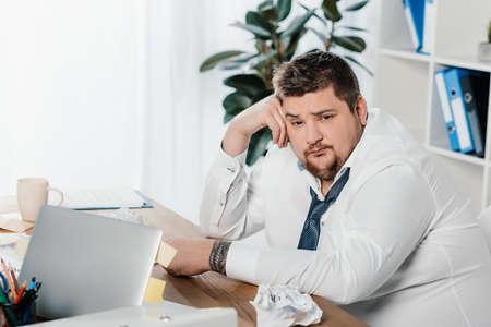 Hombre de negocios gordo sentado en el lugar de trabajo con papeles arrugados y portátil