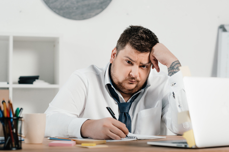 upset overweight businessman working with notepad and laptop in office