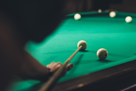 back view of cropped man playing in russian pool at bar