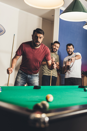 handsome frightened man scored black ball number 8 in pool Stock Photo