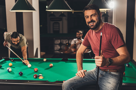 young handsome caucasian man beside billiard table in bar with friends