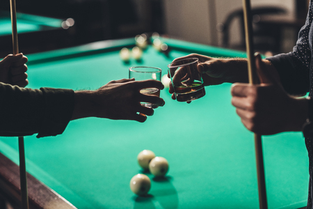 cropped image of male hands with cues and glasses with alcohol infront of billiard table at bar Stock Photo
