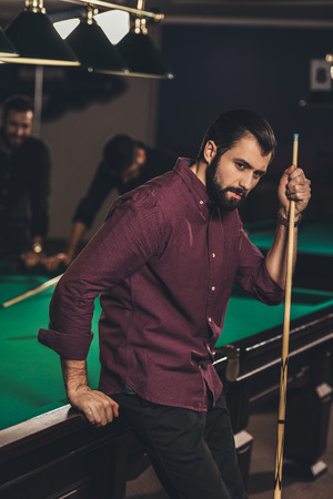 handsome caucasian man with cue beside pool table at bar with friends